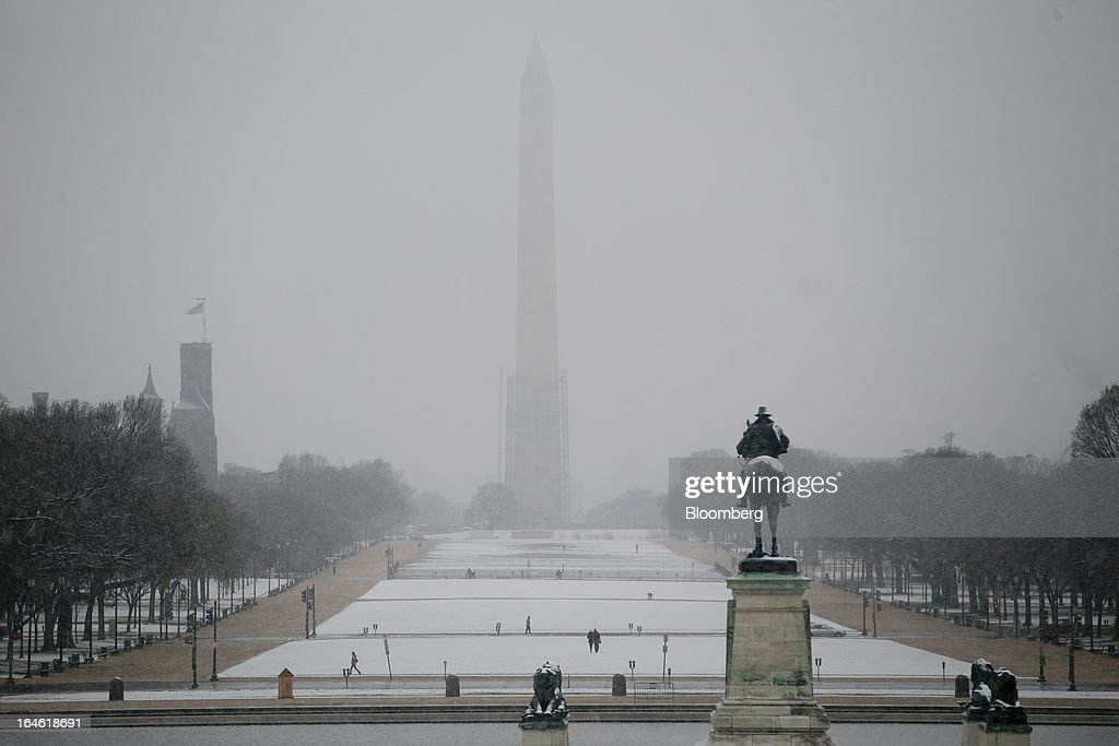 The Washington Monument is seen past snow covering the National Mall in Washington, D.C., U.S., on Monday, March 25, 2013. An early spring snowstorm tied up air traffic along the U.S. East Coast, threatening to bring 3 inches (7.6 centimeters) of slushy snow to the large cities from Washington to New York. Photographer: Andrew Harrer/Bloomberg via Getty Images