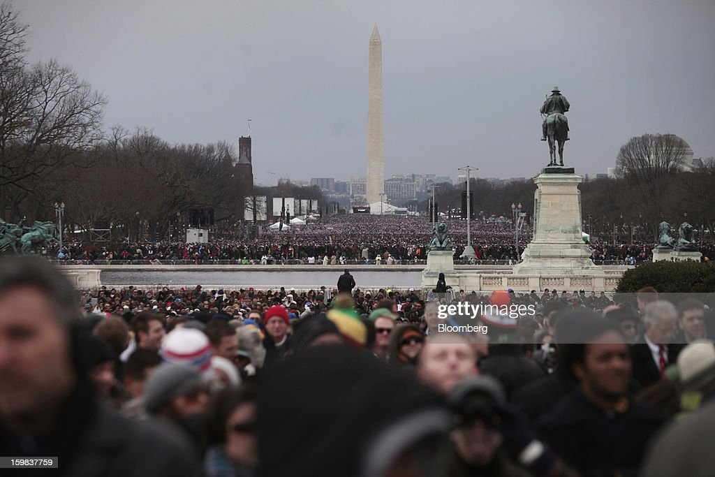 The Washington monument stands in the background, as attendees gather during the U.S. presidential inauguration in Washington, D.C., U.S., on Monday, Jan. 21, 2013. As he enters his second term President Barack Obama has shed the aura of a hopeful consensus builder determined to break partisan gridlock and adopted a more confrontational stance with Republicans. Photographer: Victor J. Blue/Bloomberg via Getty Images