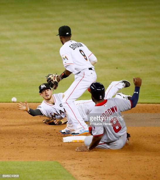 The Washington Nationals' Brian Goodwin slides safely into second base as Miami Marlins shortstop JT Riddle throws to second baseman Dee Gordon...