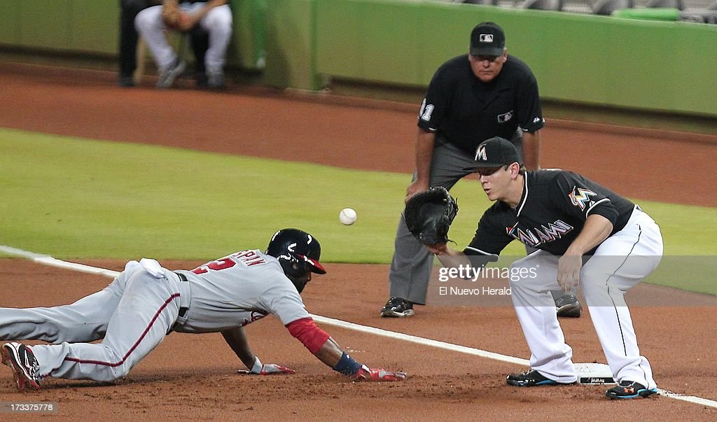 The Washington Nationals' Denard Span slides safely into first base as Miami Marlins first baseman Logan Morrison takes the throw in the first inning at Marlins Park in Miami, Florida, on Friday, July 12, 2013.