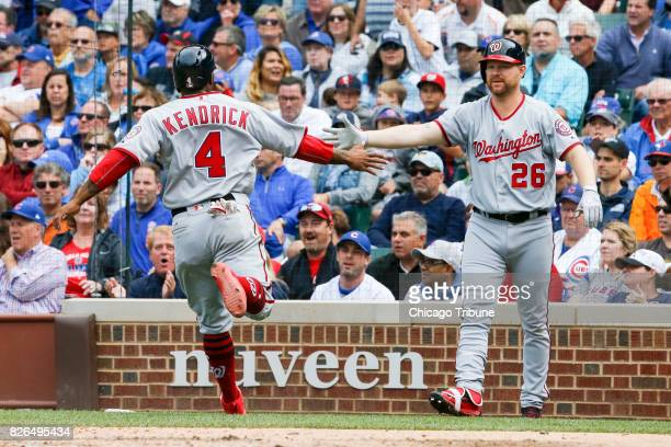 The Washington Nationals' Howie Kendrick scores on a sacrifice fly by Anthony Rendon as teammate Adam Lind greets him in the eighth inning against...