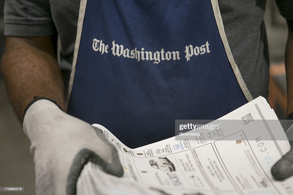 The Washington Post logo is seen on an employee's apron as he works in the run of press area of the Washington Post newspaper production facility in Springfield, Virginia, U.S., on Friday, July 12, 2013. The Washington Post began publishing on Thursday, Dec. 6, 1877, and had a circulation of 10,000. The newspaper contained four pages and cost three cents a copy. Photographer: Andrew Harrer/Bloomberg via Getty Images