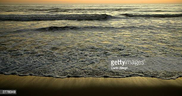 The water laps up along the beach in Santa Monica California December 2 2003 on a warm evening as much of the east coast was plunged into a deep...