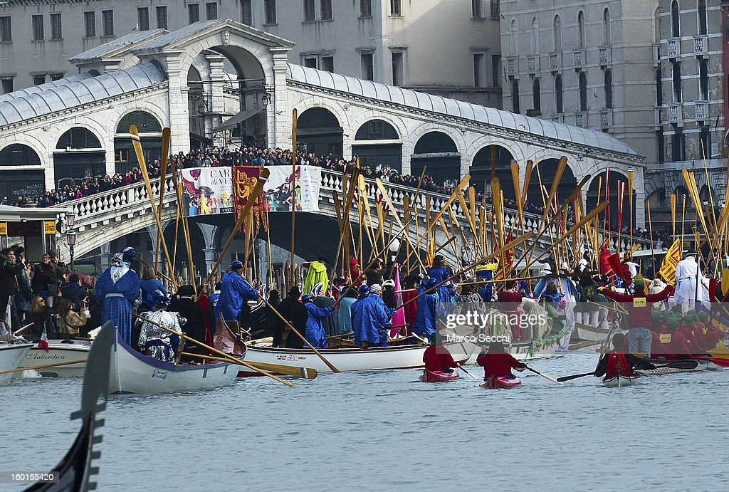 The Water Parade passes under the Rialto Bridge while rowers lift their oars to salute on January 27, 2013 in Venice, Italy. The 2013 Carnival of Venice will run from January 26 - February 12 and includes a program of gala dinners, parades, dances, masked balls and music events.