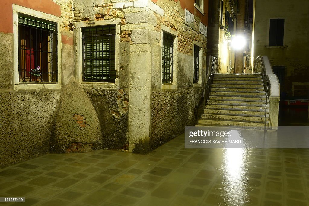 The water rises in a small street during an acqua-alta (high-water) late on February 11, 2013 in Venice. The 'acqua alta', a convergence of high tides and a strong sirocco, reached 143 centimetres around midnight.