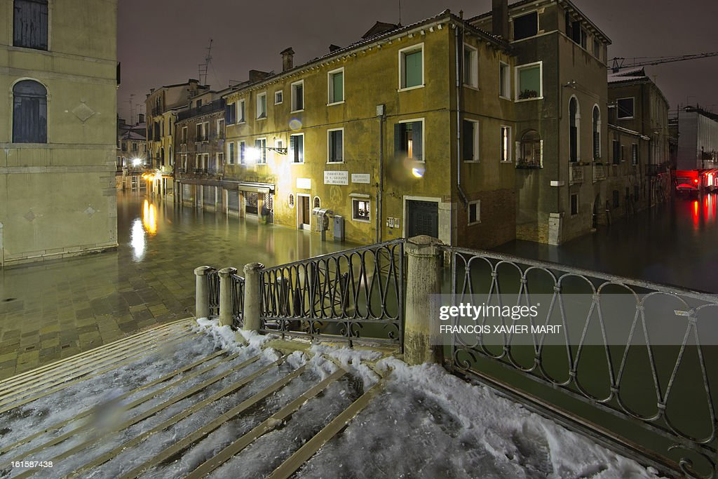 The water rises on a square during an acqua-alta (high-water) late on February 11, 2013 in Venice. The 'acqua alta', a convergence of high tides and a strong sirocco, reached 143 centimetres around midnight.