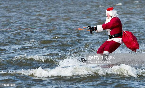 The water skiing Santa Clause heads down the Potomac River on December 24 2013 at National Harbor Maryland near Washington The group of volunteers...
