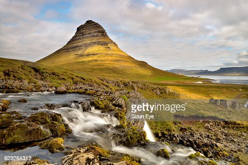 The waterfall in front of the pyramidal mountain and the sea in the background at cloudy day