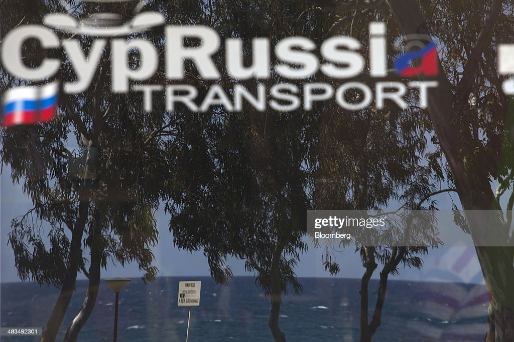 The waters of the Mediterranean Sea are reflected in the window of a CypRussi automobile hire company in Limassol, Cyprus, on Tuesday, April 8, 2014. Cyprus wants to shield financial flows with Russia, where it's the biggest foreign investor, as the U.S. and the European Union ratchet up sanctions in response to President Vladimir Putin's annexing Crimea from Ukraine. Photographer: Andrew Caballero-Reynolds/Bloomberg via Getty Images