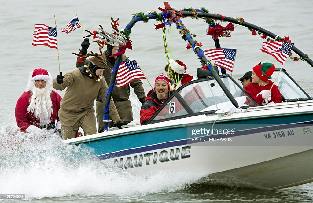 The Water-Skiing Santa Show members cruise along the Potomac River December 24, 2012 at National Harbor in Maryland, near Washington, DC, during th 27th Annual Water Skiing show. This unusual annual event features a water-skiing Santa, flying elves, the Jet-skiing Grinch, and Frosty the Snowman performing on the Potomac River. AFP PHOTO/Paul J. Richards