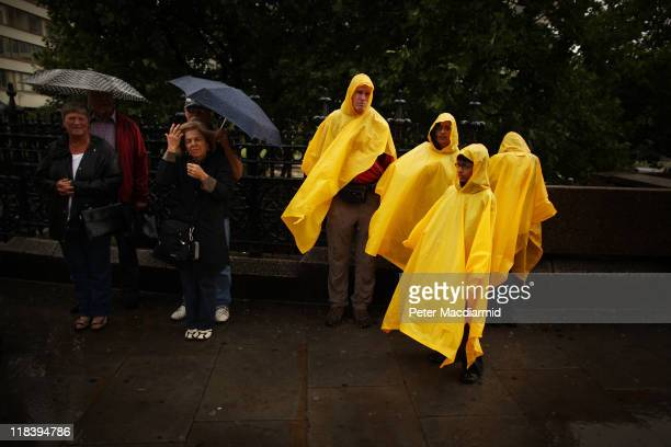 The Waugh Dube family from Berkeley California wear bright yellow ponchos as they stand near Westminster Bridge during a rain shower on July 7 2011...