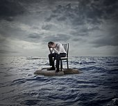 Man is sitting on a chair in the middle of the ocean