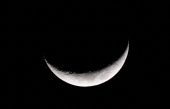 The waxing crescent moon is seen in the night sky above the San Gabriel Valley east of downtown Los Angeles on March 26 in California Sometimes...