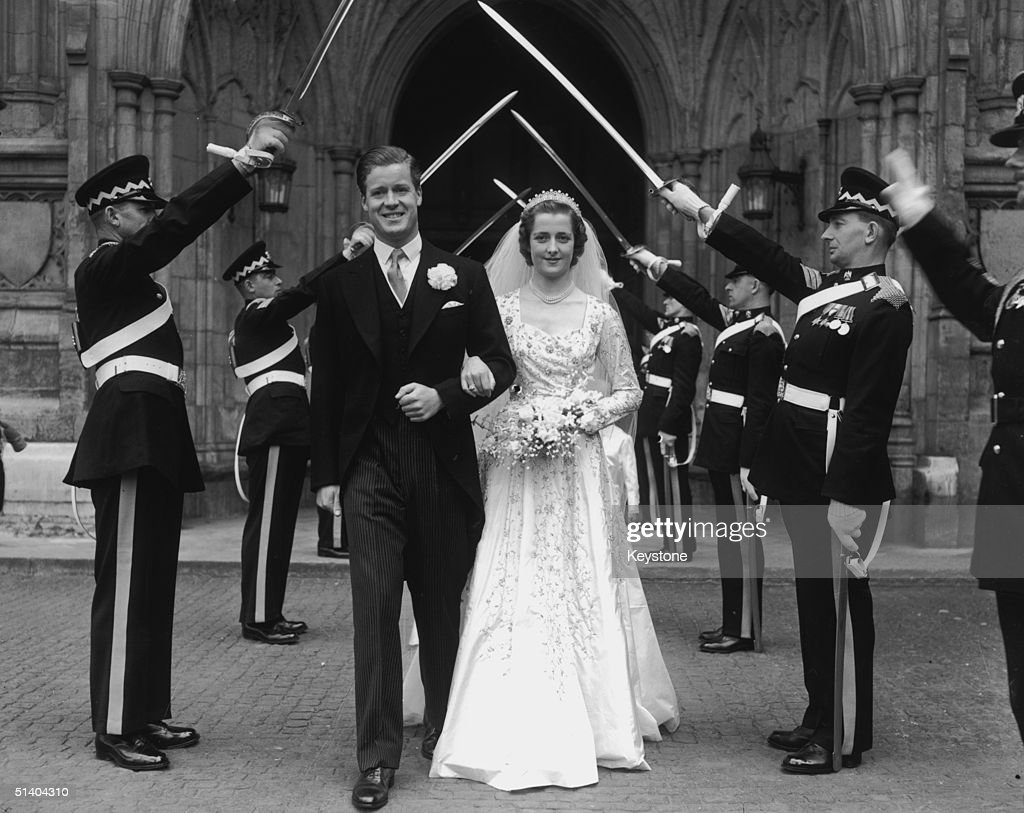 The wedding of Viscount Althorp and the Hon Frances Roche at Westminster Abbey, 1st June 1954. The bride and groom, parents of Diana Princess of Wales, are leaving the abbey through a Guard of Honour of Scots Greys.