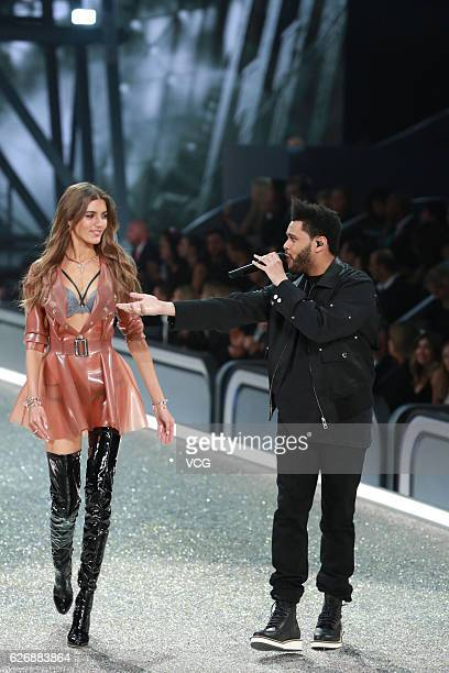 The Weeknd performs as model Valery Kaufman walks on the runway during 2016 Victoria's Secret Fashion Show on November 30 2016 in Paris France