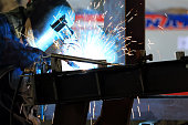 The welder is welding to structural steels with Gas metal arc welding (GMAW), also known as metal inert gas or MIG welding in the workshop.