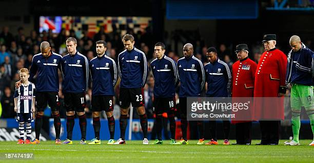 The West Brom team stand with two Chelsea Pensioners as they mark a minutes silence during the Barclays Premier League match between Chelsea and West...