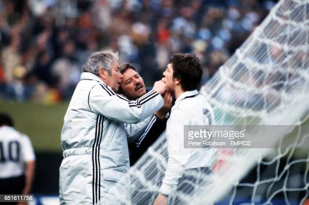 The West Germany trainers have a look at the injured Klaus Fischer