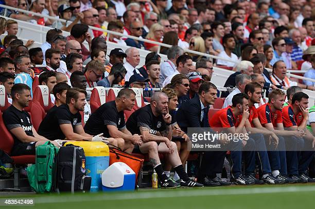 The West Ham bench looks on during the Barclays Premier League match between Arsenal and West Ham United at Emirates Stadium on August 9 2015 in...
