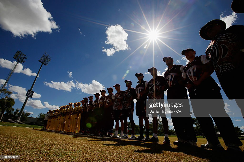 The Western Australia and Queensland teams link arms before their first match during the National Indigenous Cricket Championships on February 8, 2016 in Alice Springs, Australia.