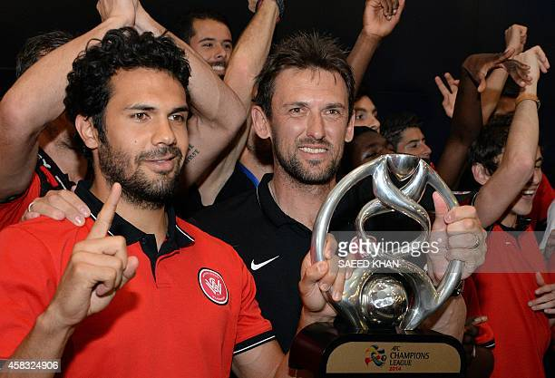 The Western Sydney Wanderers' coach Tony Popovic and captain Nikolai ToporStanley hold the AFC Champions League trophy upon team's arrival at Sydney...