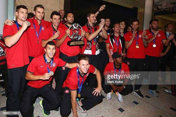 The Western Sydney Wanderers team pose with the trophy at Sydney International Airport after arriving from Saudi Arabia after victory over Al Hilal...