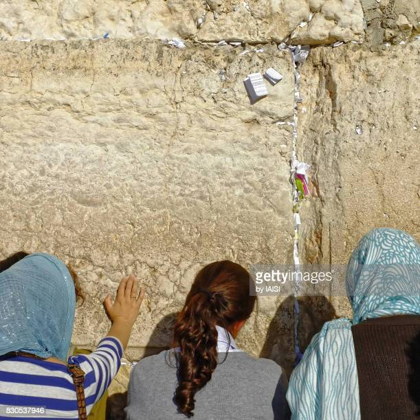 The Western Wall, the womens side, three women praying, and prayer notes placed in the crevices of the wall