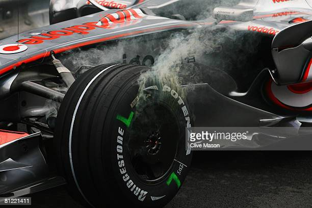 The wheels and tyres of the car of Heikki Kovalainen of Finland and McLaren Mercedes smoke after he span out while going through the swimming pool...