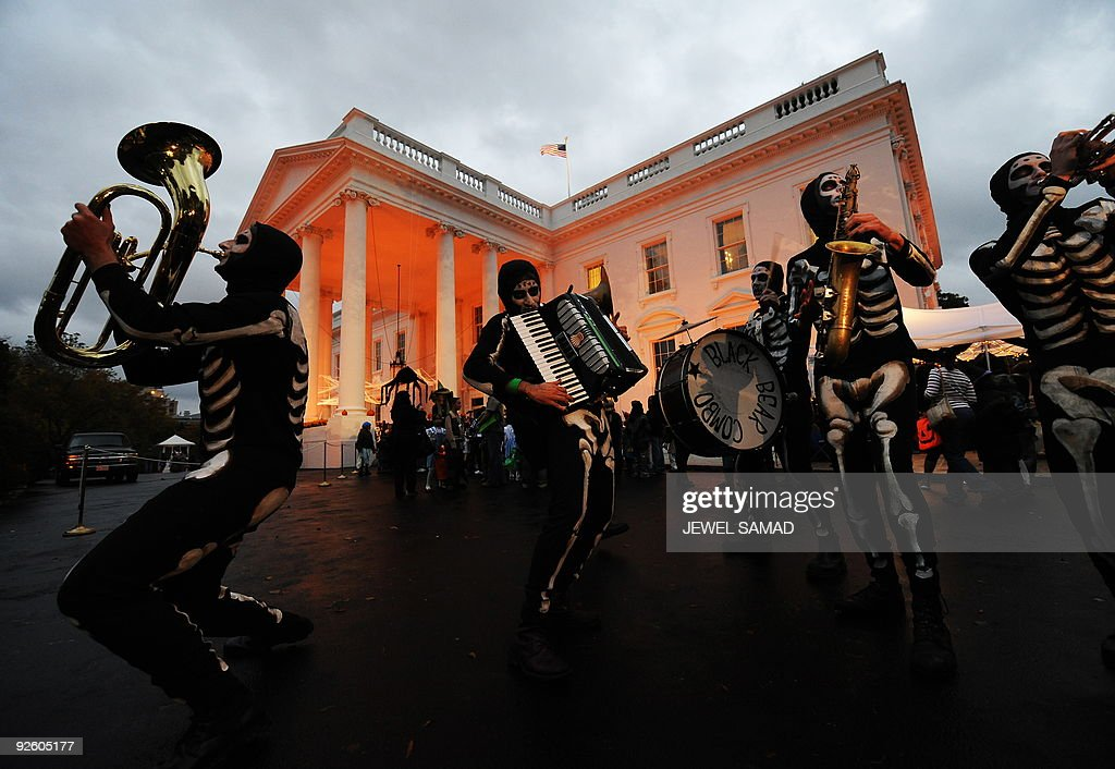 The White House is lit with orange light as a group of 'skeletons' perform at the North Portico of the White House in Washington on October 31, 2009. US President Barack Obama and First Lady Michelle Obama will greet more than 2,000 children from Washington, Maryland and Virginia schools and their families to celebrate Halloween. AFP PHOTO/Jewel SAMAD