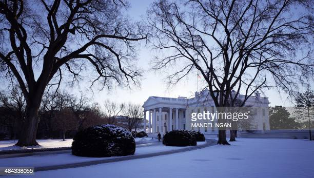 The White House is seen behind a lawn blanketed with snow on January 22 2014 in Washington DC The northeastern US shivered amid heavy snowfall and...