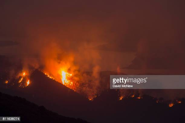 The Whittier Fire burns next to Lake Cachuma on July 9 2017 near Santa Barbara California The Whittier Fire and the Alamo Fire together have...
