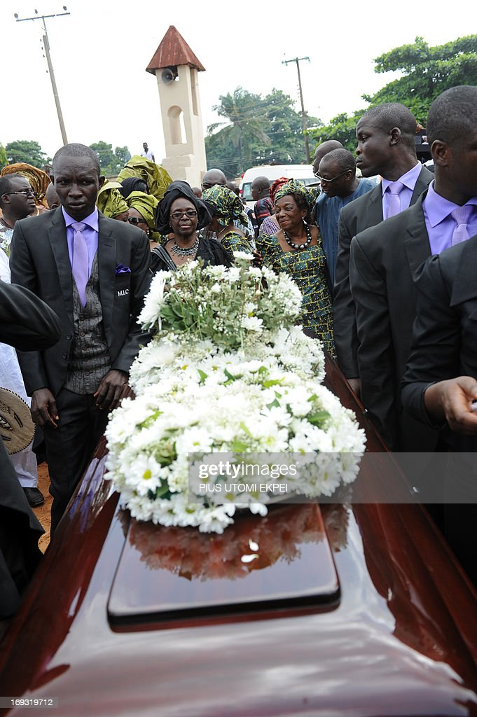 The widow of author Professor Chinua Achebe, Professor Christie Achebe (C) accompanies the casket of her husband during the funeral service of the late author at Ogidi in southeast Nigeria on May 23, 2013. Renowned author Professor Chinua Achebe was buried at his Ogidi country home. Hundreds of mourners gathered on Thursday in the hometown of Nigerian novelist Chinua Achebe for the funeral of the man regarded as the father of modern African literature and the author of the widely praised 'Things Fall Apart.'
