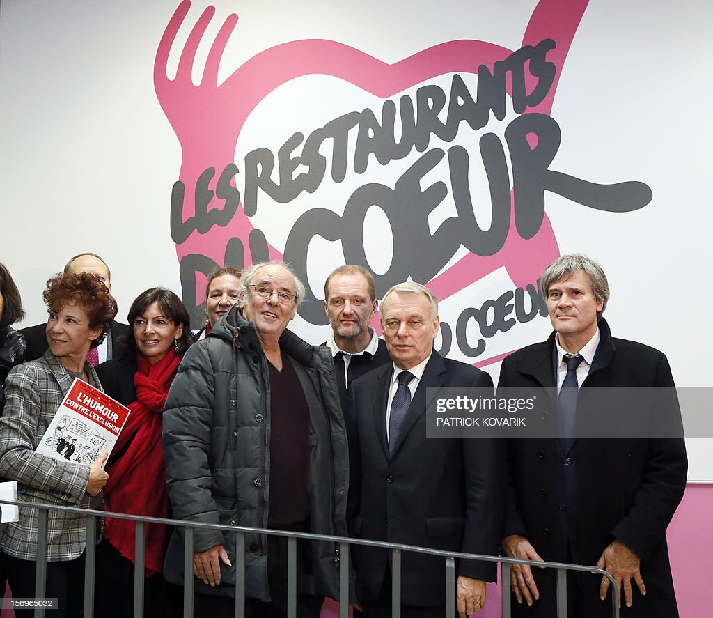 The widow of French entertainer and founder of French charitable organisation 'Les Restos du Coeur' (Restaurants of the Heart), Coluche, Veronique Colucci, Paris deputy mayor Anne Hidalgo, French singer Maxime Leforestier, the president of 'Les Restos du Coeur', Olivier Berthe, French Prime Minister Jean-Marc Ayrault and French Agriculture Minister Stephane Le Foll participate on November 26, 2012 in Paris in the launching of the 28th winter campaign to distribute food to the needy.