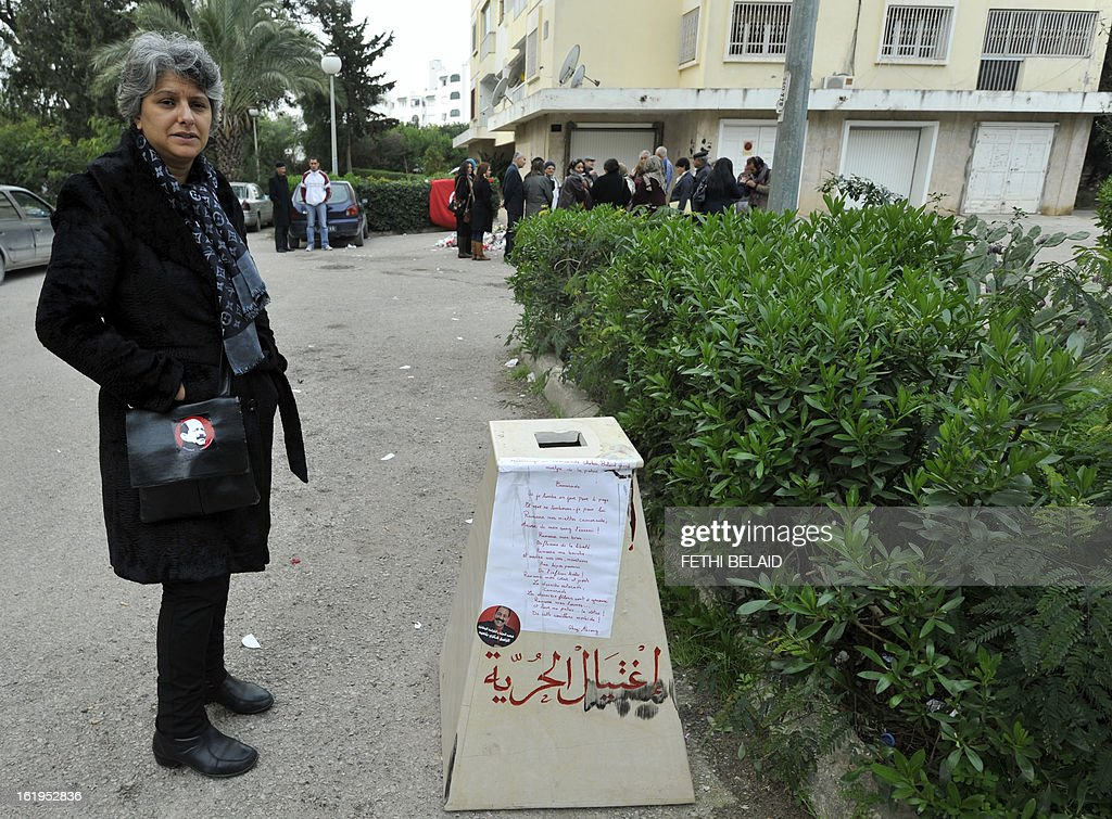 The widow of murdered opposition figure Chokri Belaid, Besma Khalfaoui, stands in front of the vandalised and broken statue erected in his honour, on February 18, 2013, in Tunis. The memorial, installed as a work of contemporary art by Tunisian artists, was ripped off from its base and broken, and the flowers surrounding it were trampled and scattered. Belaid, a leftist leader and fierce critic of Tunisia's ruling Islamist-led government, was shot dead by a gunman as he left his home.