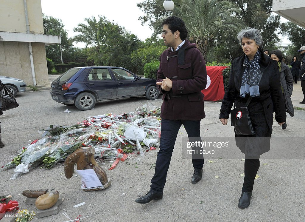 The widow of murdered opposition figure Chokri Belaid, Besma Khalfaoui, walks past the vandalised and broken statue erected in his honour, on February 18, 2013, in Tunis. The memorial, installed as a work of contemporary art by Tunisian artists, was ripped off from its base and broken, and the flowers surrounding it were trampled and scattered. Belaid, a leftist leader and fierce critic of Tunisia's ruling Islamist-led government, was shot dead by a gunman as he left his home. AFP PHOTO / FETHI BELAID