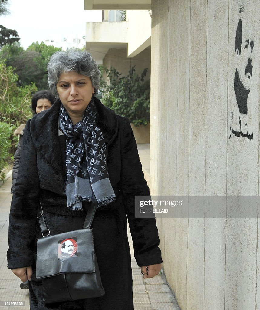 The widow of murdered opposition figure Chokri Belaid, Besma Khalfaoui, arrives at the site of the vandalised and broken statue erected in his honour, on February 18, 2013, in Tunis. The memorial, installed as a work of contemporary art by Tunisian artists, was ripped off from its base and broken, and the flowers surrounding it were trampled and scattered. Belaid, a leftist leader and fierce critic of Tunisia's ruling Islamist-led government, was shot dead by a gunman as he left his home. is seen left.