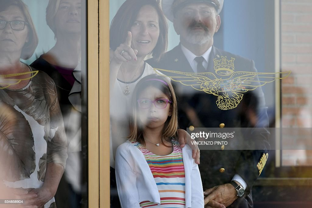 The wife (C) and the daughter of Italian Marine Salvatore Girone wait for his arrival on May 28, 2016 at the Ciampino airport in Rome. India's top court on May 26, 2016 allowed Girone accused of killing two fishermen to return home pending a ruling on where he should be tried in a long-running case that has soured ties between the two countries. Salvatore Girone and fellow marine Massimiliano Latorre are accused of shooting the fishermen while protecting an Italian oil tanker as part of an anti-piracy mission off India's southern Kerala coast in 2012. / AFP / VINCENZO