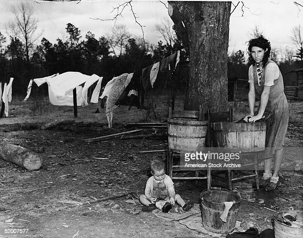 The wife of a tenant farmer scrubs laundry on a washboard in a wooden tub while a dirtcovered toddler plays with an empty bottle on the ground North...