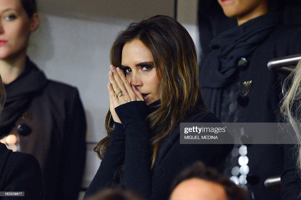 The wife of British football player David Beckham, Victoria Beckham (C) is pictured in the stands during the French L1 football match Paris Saint-Germain (PSG) vs Olympique de Marseille (OM) on February 24, 2013 at the Parc des Princes stadium in Paris. AFP PHOTO MIGUEL MEDINA