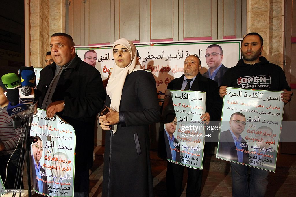 The wife of hunger striking Palestinian prisoner Mohammed al-Qiq, Fayha Shalash (C), and his brother speak during a press conference in the West Bank town of Hebron on February 12, 2016. Qiq, 33, a correspondent for Saudi Arabia's Almajd TV network, was arrested on November 21 at his home in the West Bank city of Ramallah and placed under administrative detention, an Israeli procedure allowing indefinite imprisonment without trial. / AFP / HAZEM BADER