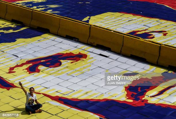 The wife of jailed Venezuelan opposition leader Leopoldo Lopez Lilian Tintori sits on top of a giant image of him during a demonstration held on the...