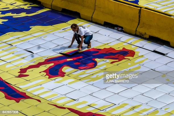 The wife of jailed Venezuelan opposition leader Leopoldo Lopez Lilian Tintori lays down one of the pieces of a giant image of him during a...