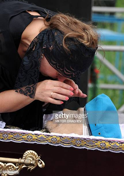 The wife of late Vasily Burov gestures as she looks at his face during his funeral at a cemetery in the eastern Ukrainian city of Makiyivka near...