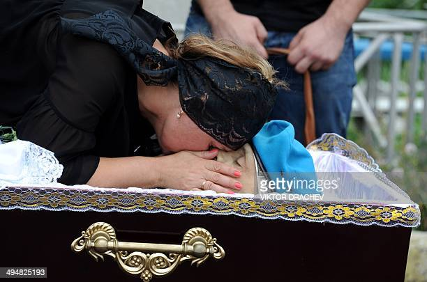 The wife of late Vasily Burov kisses his face during his funeral at a cemetery in the eastern Ukrainian city of Makiyivka near Donetsk on May 31 2014...