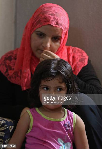 The wife of Syrian refugee Mohamed Ghazal sit with one of their children a home in the northern Jordanian city of Irbid where they are being housed...