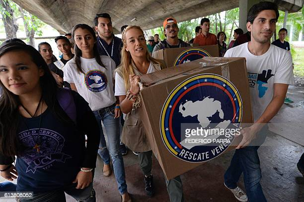 The wife of Venezuelan jailed opposition leader Leopoldo Lopez Lilian Tintori helps carry a box during a gathering to donate supplies to students of...