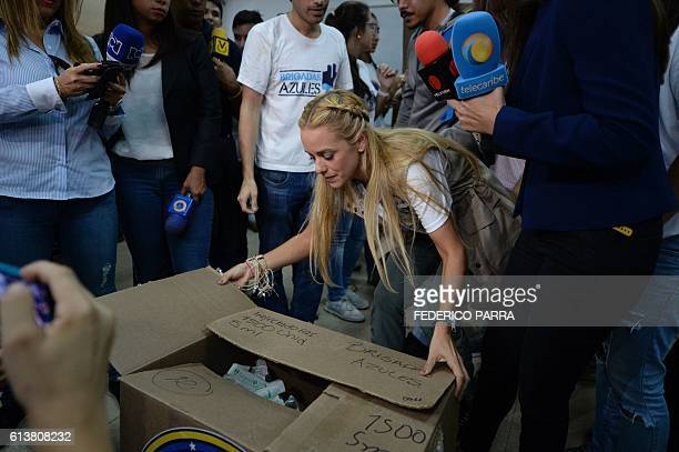 The wife of Venezuelan jailed opposition leader Leopoldo Lopez Lilian Tintori opens a box during a gathering to donate supplies to students of the...