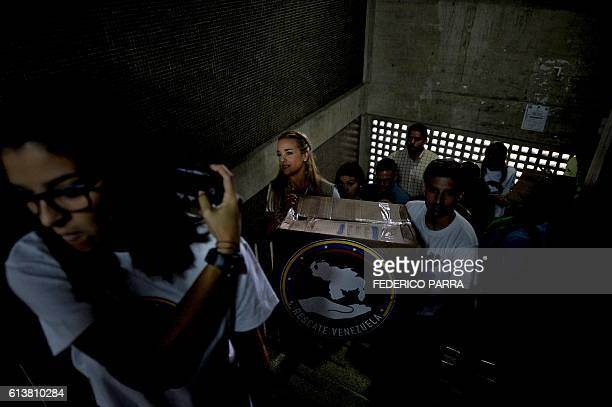 The wife of Venezuelan jailed opposition leader Leopoldo Lopez Lilian Tintori and members of social groups carry a box before donating supplies to...