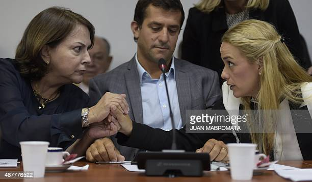 The wife of Venezuelan opposition leader Antonio Ledezma Mitzy Capriles and Lilian Tintori wife of opposition leader Leopoldo Lopez hold hands during...