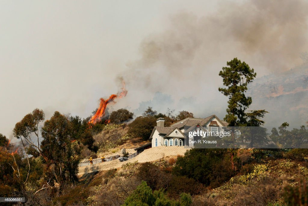 The wildfires burn through the hillsides nearing homes on January 16, 2014 in Glendora, California. A wildfire near Glendora in the San Gabriel Valley has prompted officials to order evacuations for houses near the fire.